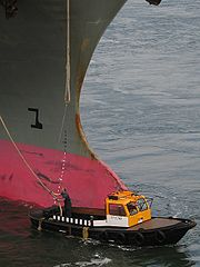 180px-Mooring_boat_with_container_ship